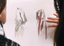 Students studying fashion design sketches