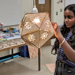 Student putting together her laser cut lamp in the summer camp, 3-D Modeling & Printing