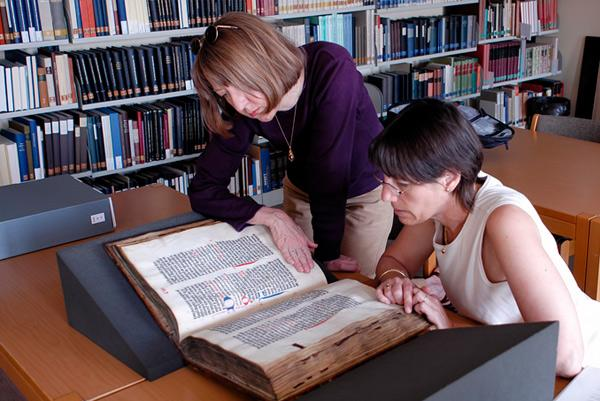 faculty researchers studying an old book
