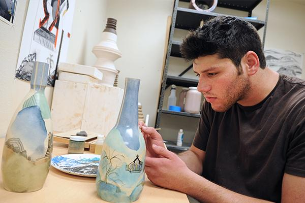 Ceramics Student painting his work