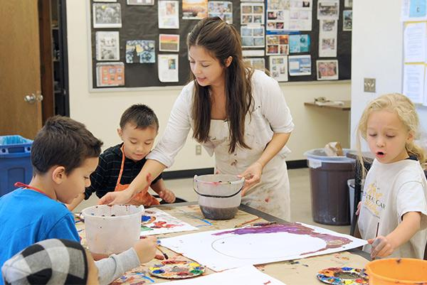 ASU grad student teaching painting to young children