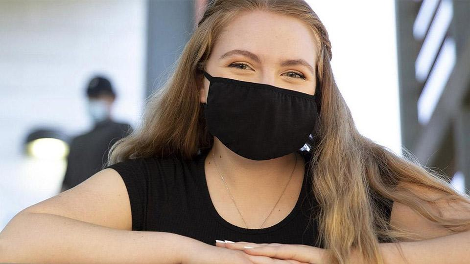 woman leaning on a railing wearing a black face mask