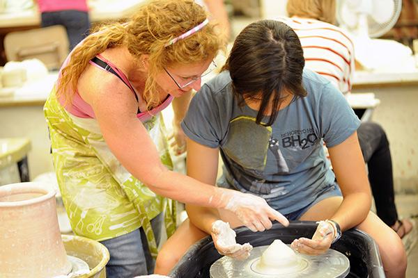 Professor Susan Beiner helped student with her ceramics work